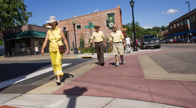 Pedestrians using a colored-concrete crosswalk.