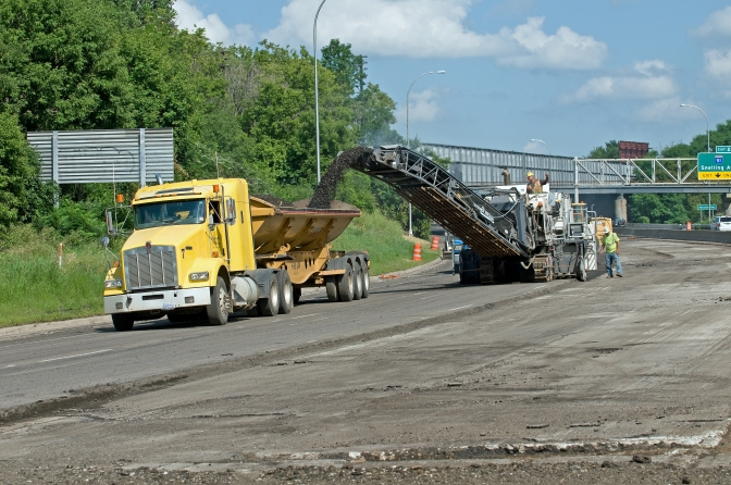 A road crew performs a mill-and-overlay maintenance operation on a road.