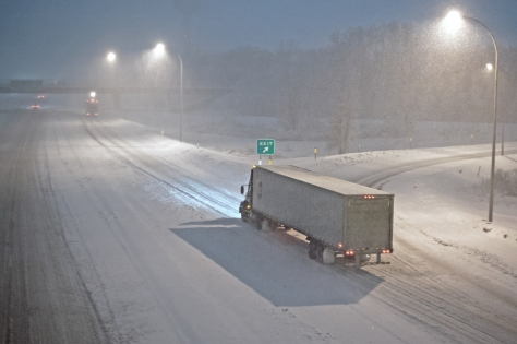 A semi truck driving on a snowy highway.