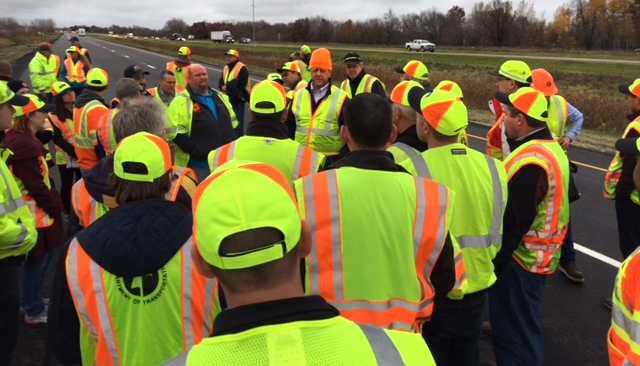 Crowd of engineers near highway with pavement test sections