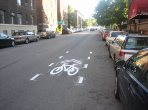 Pavement markings with directional arrows and a bicycle icon, called sharrows.