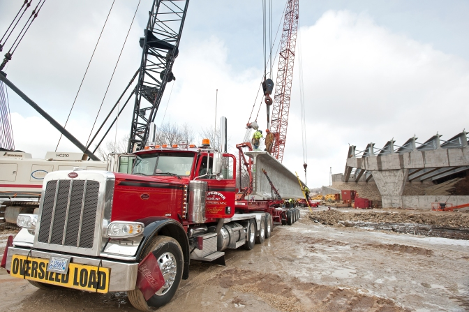 "Bridge crews unload a huge precast I-beam girder off the bed of a tractor-trailer that is marked with red flags and an ""Oversized Load"" banner."