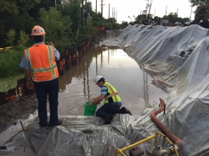 A worker collects a sample of construction site stormwater runoff in a plastic-lined settling pond while another looks on.