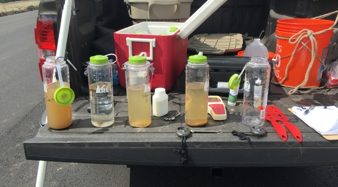 Components of the Tailgate Test Kit, including five bottles with water samples of varying turbidity, buckets and coolers.