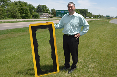 Man holding frame of stop sign with reflective tape