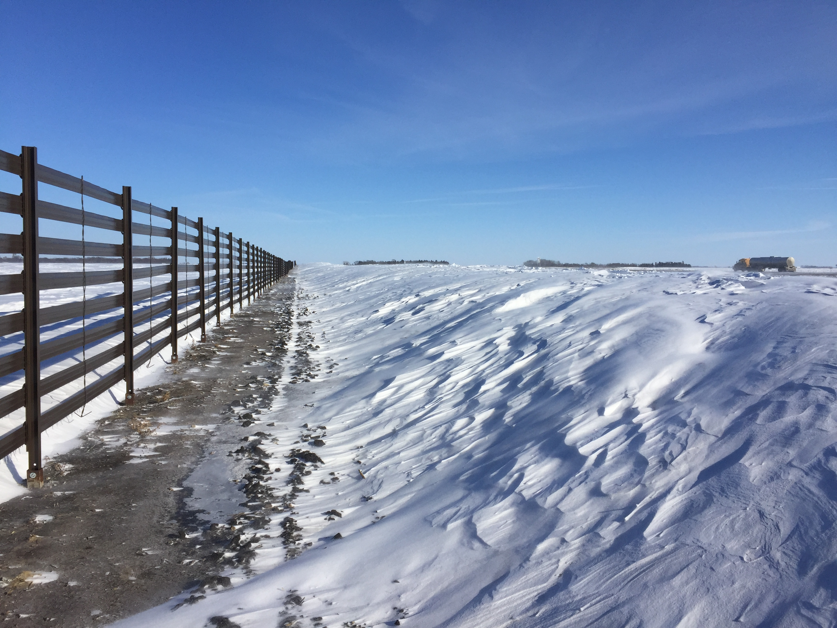 A permanent snow fence along a rural highway.