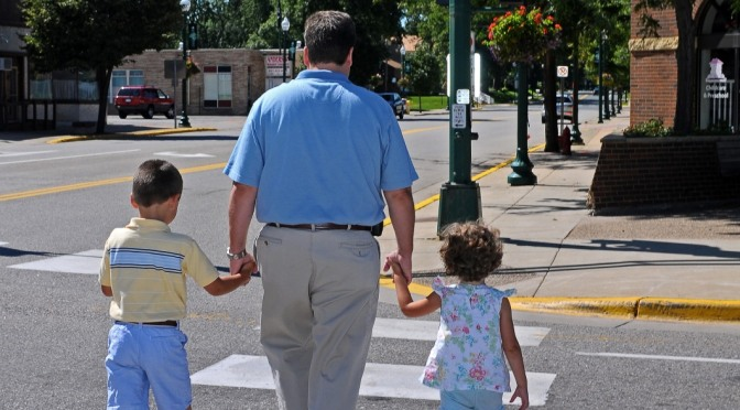 Family crossing street at a marked crosswalk