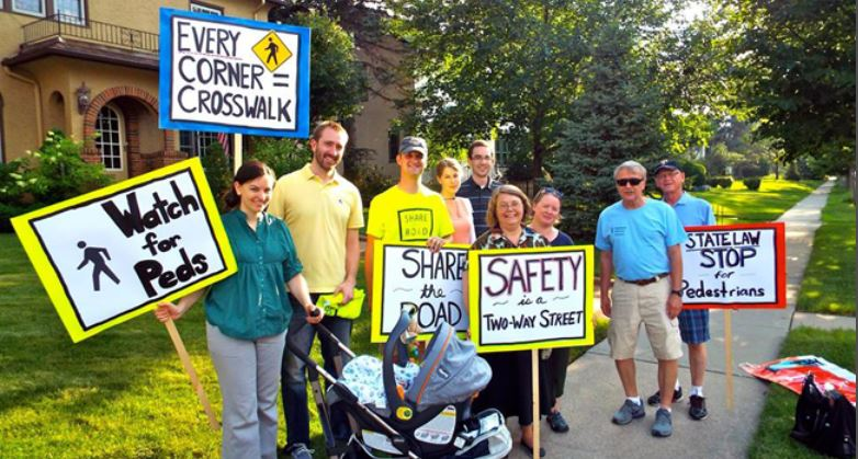 A group of people holding signs with traffic safety messages
