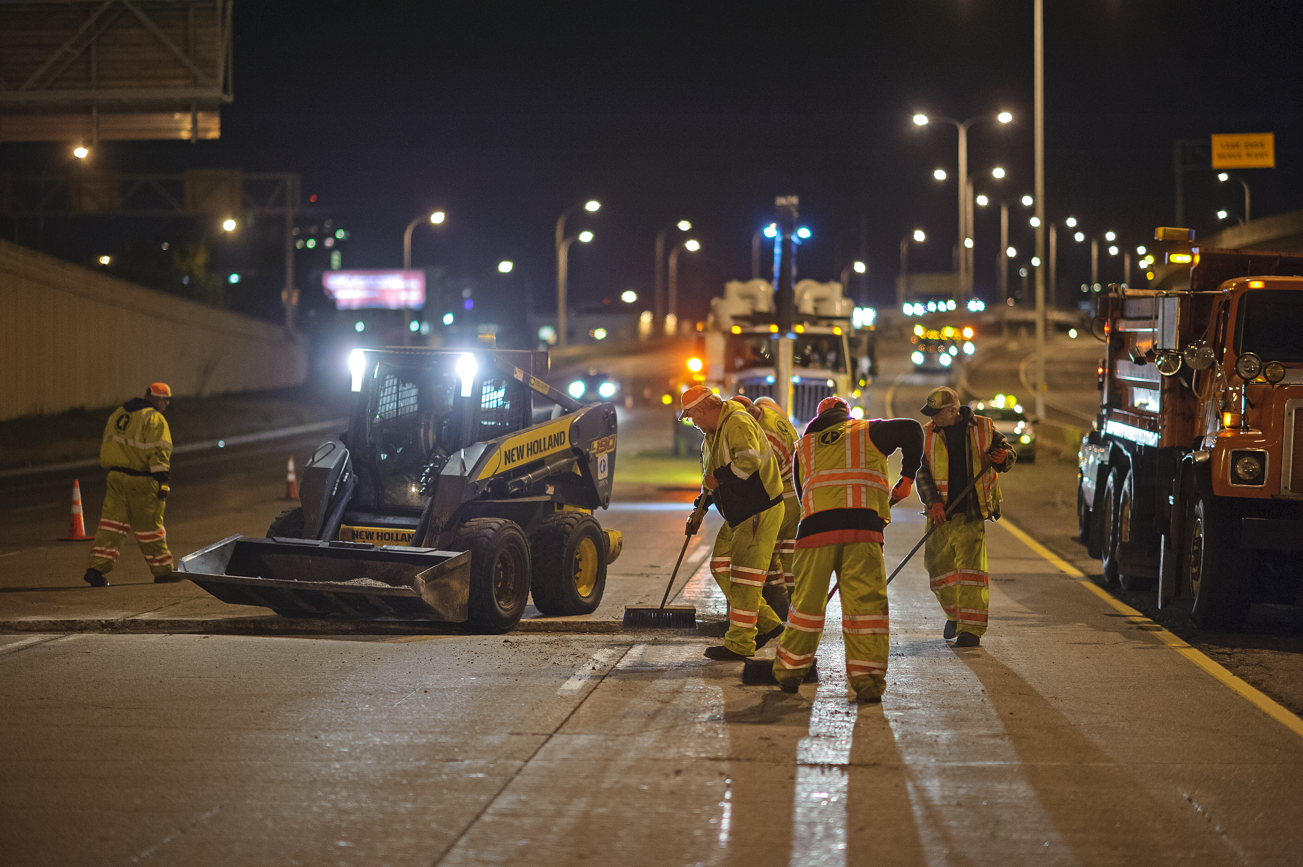 A nighttime view of workers and heavy equipment at a road construction site