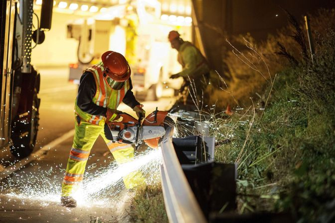 worker on highway using a saw to repair guardrail