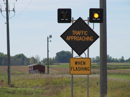 Dynamic Warning sign on a rural road that says traffic approaching when flashing