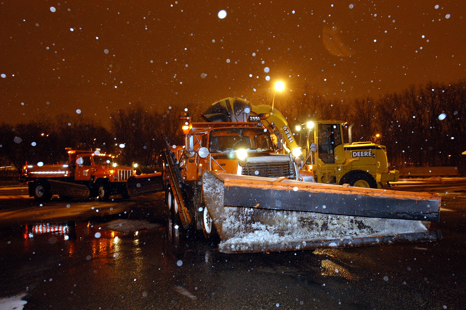 Snowplows and other winter maintenance vehicles clearing roads during a nighttime snowstorm.