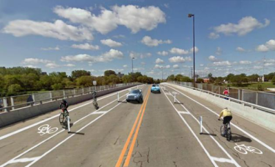 Two lane road with bicycle lanes on both sides of the road with cars on the road and cyclists in the bike lanes.