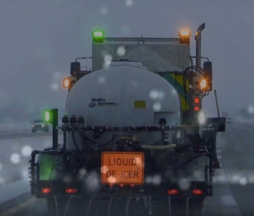 Maintenance truck applying liquid de-icer on highway