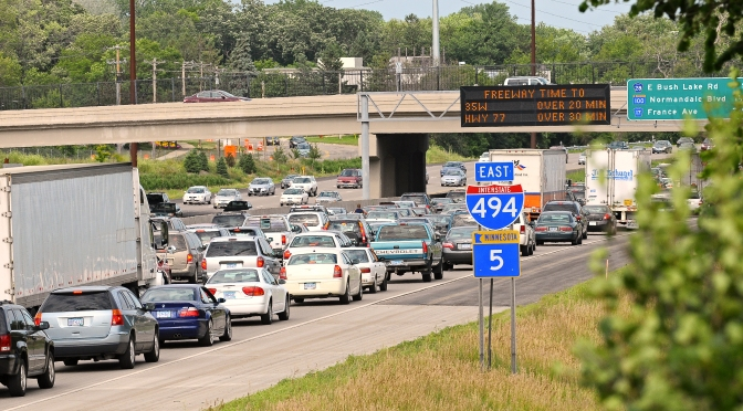 Interstate 494 with heavy traffic congestion. Overhead sign shows estimated time to other highways