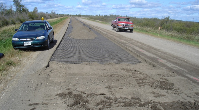 Truck and a car on a rural highway with geogrid applied to the road