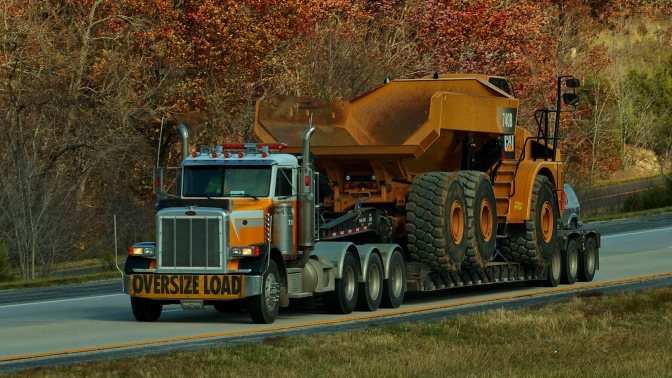 Semi-tractor with oversize load banner, hauling a large construction vehicle