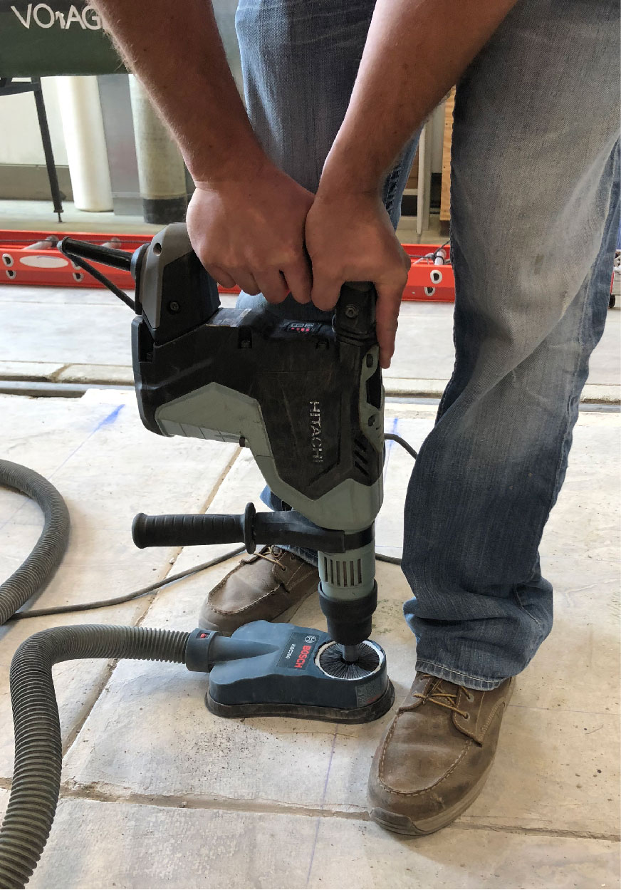 A researcher uses a dust-collecting drill to ensure clean insertion of rebar in concrete.