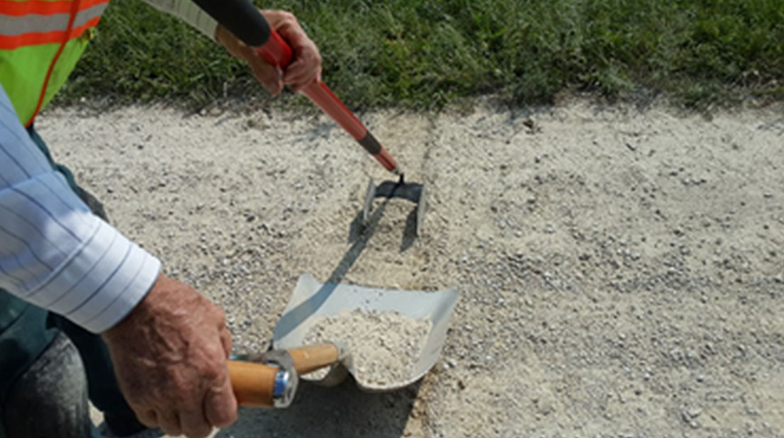 A researcher scrapes a gravel road surface with a modified garden hoe to measure loose aggregate levels.