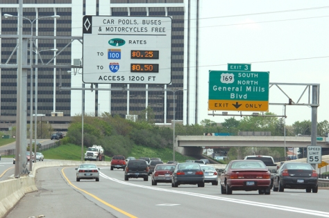 A MnPASS lane on Interstate 394 at the General Mills Boulevard exit. The express lane is closest to the highway median, indicated by a white diamond-shaped marker on the pavement and separated from three other traffic lanes by a solid white line. A highway sign above the lane indicates the fees for lane use.