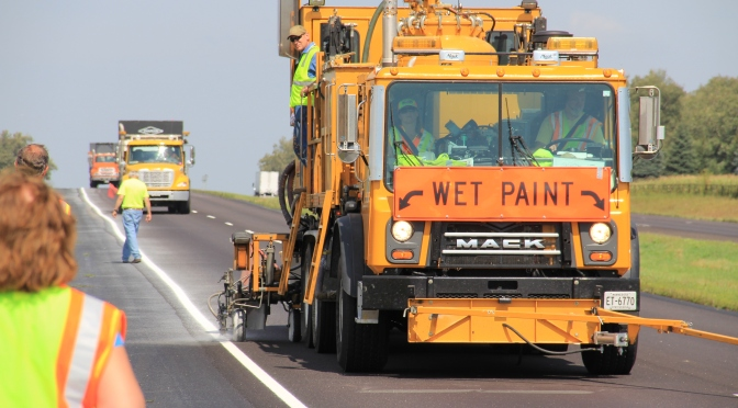 A striping truck applies new edge lines on a resurfaced roadway.