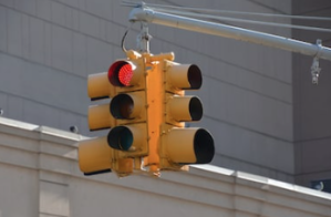 A four-sided traffic signal hangs from a pole over an intersection. The traffic light illuminated on the visible side is red.