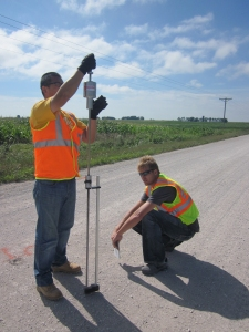 Two researchers test the base structural strength of a rural pavement using a dynamic cone penetrometer.