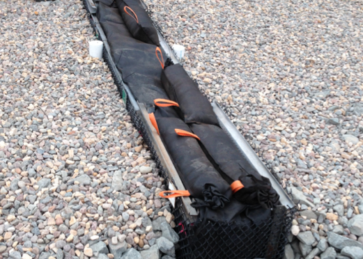 A wide expanse of washed stones holds a 12.5-foot-long by 16-inch-wide section of a buried black geotextile container spanning the width of the gravel. The black fabric is supported by a metal structure above the stones. Orange loop handles are visible on parts of the geotextile container.