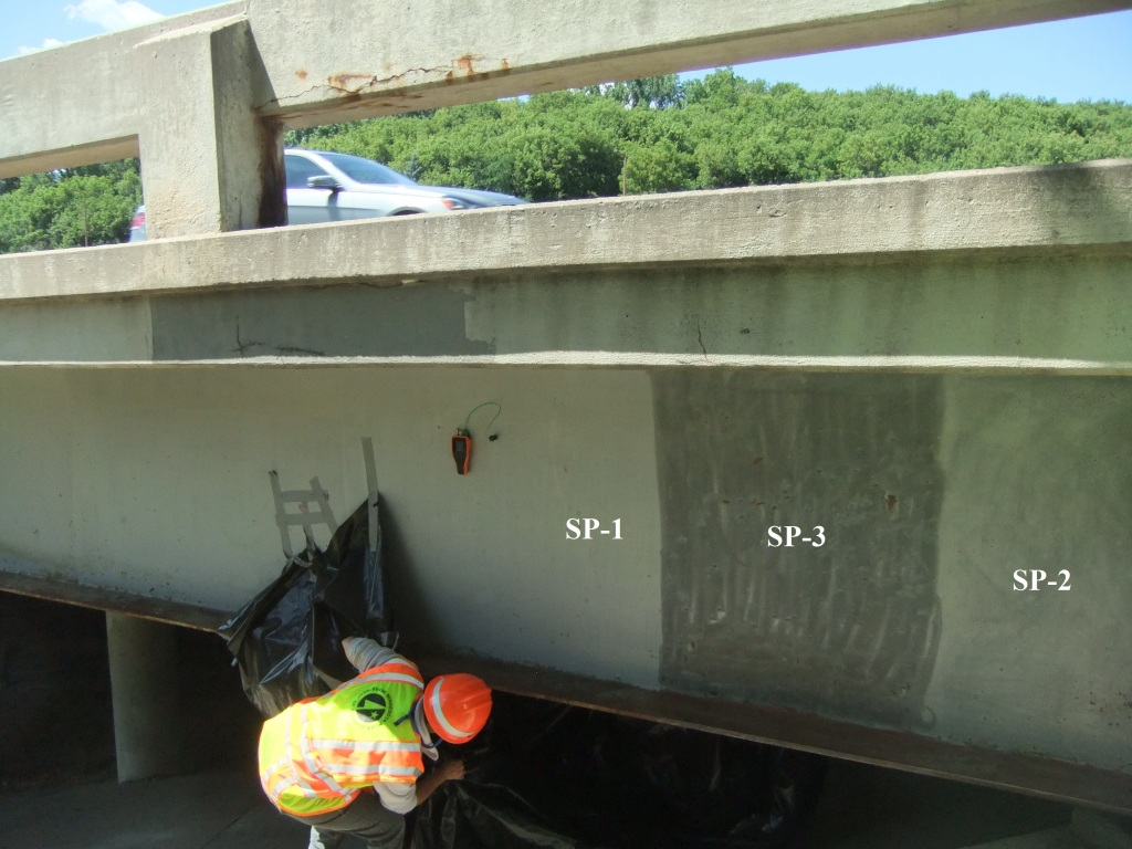 A crew member investigates and records surface preparation conditions on a section of steel beam before new coatings are applied. The surface preparation level of three areas is noted: SP-1, SP-2 and SP-3.