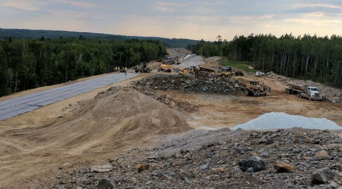 Piles of rock, sand and other neutral materials at a construction site in northern Minnesota where crews and large trucks work to lay the bed for a new road.
