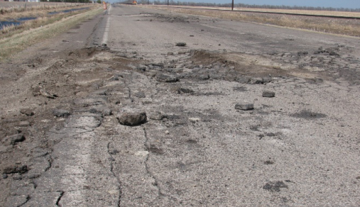 A rural asphalt road shows badly deteriorated areas, with cracks and holes in the asphalt.