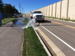 A water tanker truck on an asphalt street applies water to a median strip of new turfgrass using a nozzle on the front of the truck. A long spray of water soaks the grass and sidewalk.