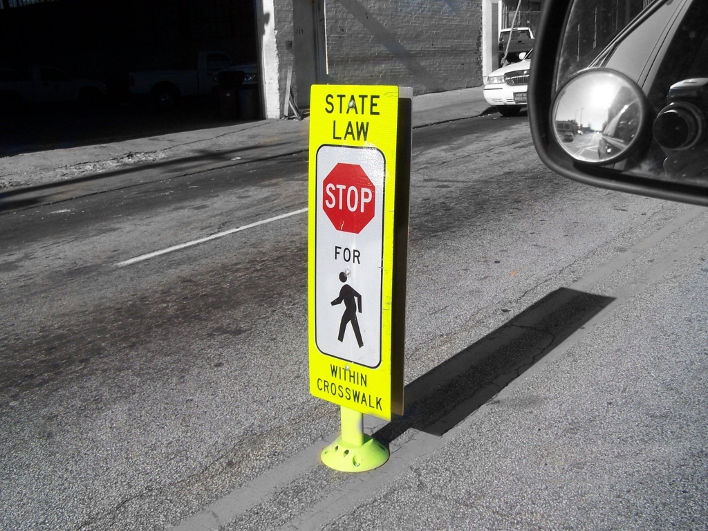 "In-street pedestrian crossing sign with the message ""State law: Stop for pedestrians within crosswalk."""