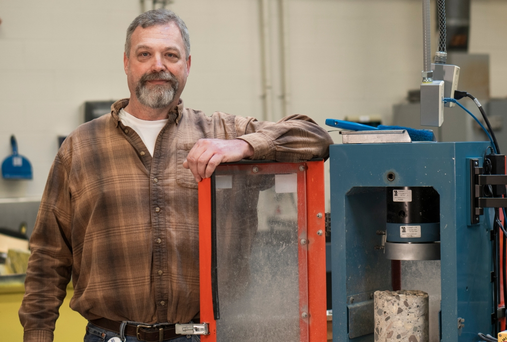 Pavement rehabilitation expert Gordon Bruhn stands beside laboratory equipment that will test a concrete pavement core's compressive strength.