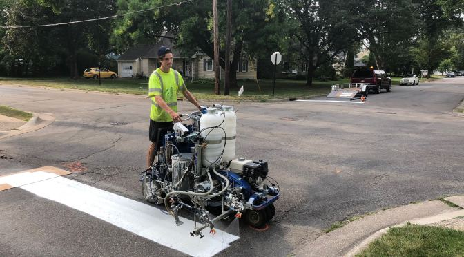 A crew member in a yellow visibility vest installs a white stop line with a pavement marking installer at a two-lane intersection. The wheeled machine, guided by hand, consists of two white plastic paint tanks, hoses and a sprayer apparatus on a low-powered base.