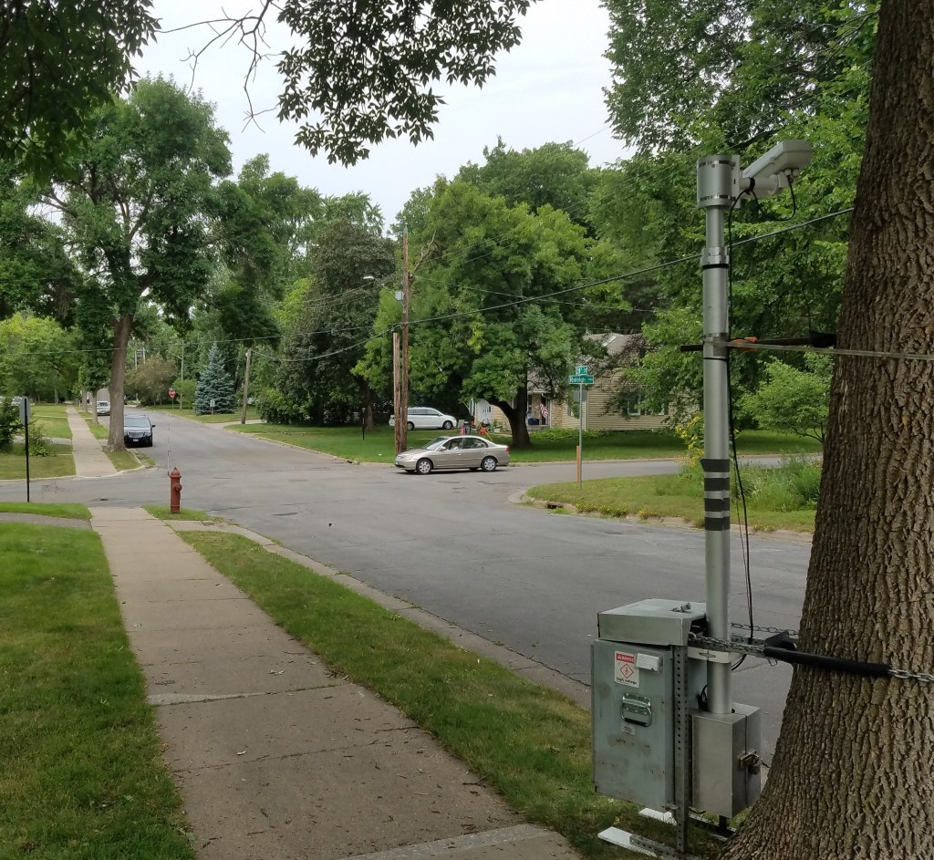A tall video camera with enclosed power source is attached to a tree near the sidewalk along a two-lane city street.