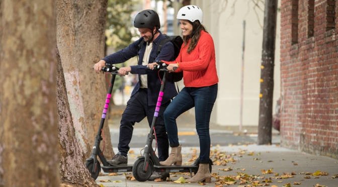Two young adults, wearing helmets use e-scooters.