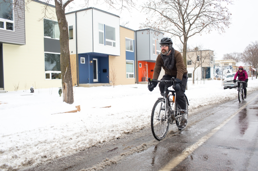 Two cyclists use a bicycle path on an urban street in the snow.
