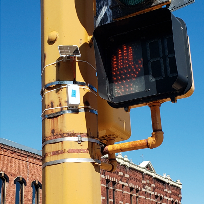 A small, white rectangular BLE beacon is attached to a traffic signal pole near the pedestrian signal light.