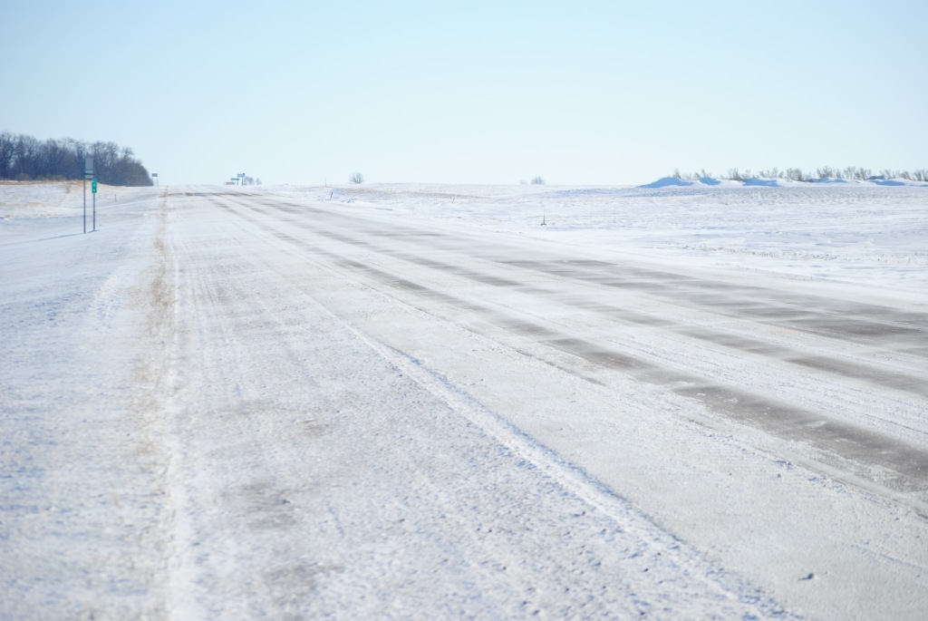 Cross-road snow drifting at a rural control site on a clear day.