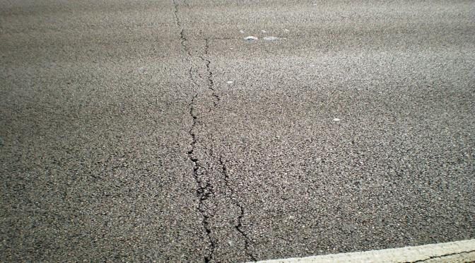 Cracks across a full lane of asphalt pavement.
