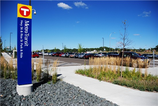 A park-and-ride sign for Metro Transit marks the corner of a large parking lot for transit users' cars.