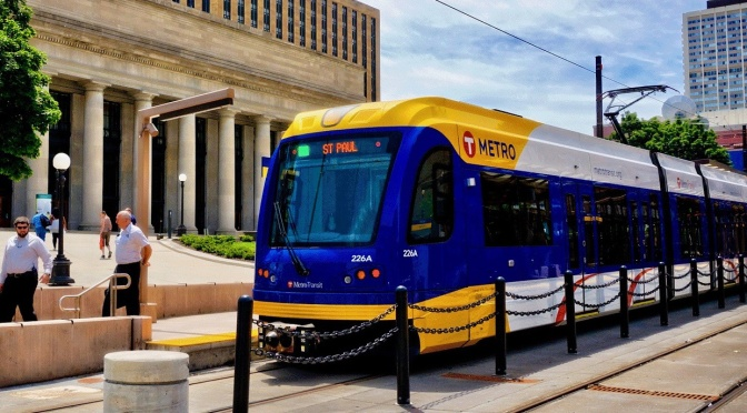 A Metro Transit light rail train stops near a downtown building.